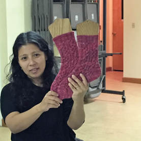 Woman holding up two pink socks on wooden sock blockers